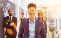 Lächelnder asiatischer Start-Up Geschäftsmann mit Business Team im Büro